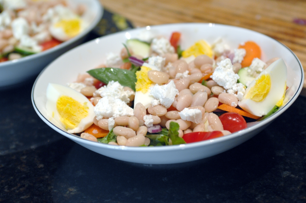 Green salad with white beans, boiled eggs, veggies and a champagne vinaigrette from http://www.oneishungry.com